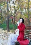 Η ανώνυμη γυναίκα που απολαμβάνει το take-$l*away φλυτζάνι καφέ την ηλιόλουστη κρύα ημέρα πτώσης κάθεται στον πάγκο στοκ εικόνες