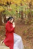 Η ανώνυμη γυναίκα που απολαμβάνει το take-$l*away φλυτζάνι καφέ την ηλιόλουστη κρύα ημέρα πτώσης κάθεται κάτω από το δέντρο στοκ εικόνες