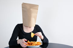 Η ανώνυμη γυναίκα τρώει τυφλά τα ανθυγειινά τρόφιμα στοκ φωτογραφίες