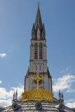 Η ανώτερη βασιλική με τον επιχρυσωμένο σταυρό αγγελιών κορωνών σε Lourdes στοκ εικόνες