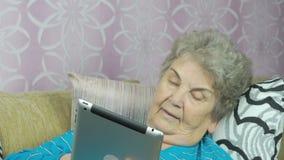Η ανώτερη γιαγιά κρατά έναν υπολογιστή ταμπλετών στο εσωτερικό απόθεμα βίντεο