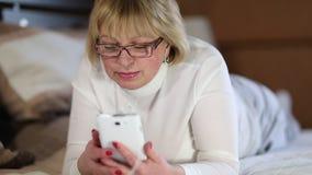 Η ανώτερη γυναίκα βρίσκεται στον καναπέ και ακούει τη μουσική με τις ιδιαίτερες προσοχές απόθεμα βίντεο