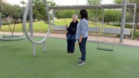 Η ανώτερη γυναίκα ζητά από την κόρη για να την ωθήσει στην ταλάντευση όπως στις παλιές καλές μέρες απόθεμα βίντεο