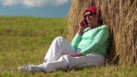 Η ανώτερη γυναίκα κάθεται κοντά στη θυμωνιά χόρτου και επικοινωνεί μέσω του κινητού τηλεφώνου απόθεμα βίντεο