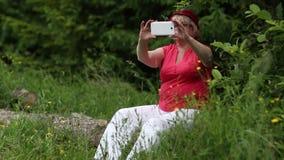 Η ανώτερη γυναίκα κάθεται σε ένα πεσμένο δέντρο στο δάσος και κάνει τις φωτογραφίες στο smartphone απόθεμα βίντεο