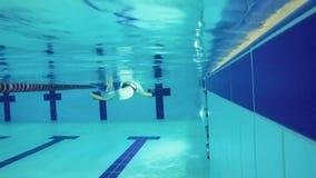 Η ανώτερη γυναίκα κολυμπά με τον ειδικό εξοπλισμό στην πισίνα - υποβρύχια απόθεμα βίντεο