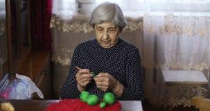 Η ανώτερη γυναίκα με την γκρίζα τρίχα και τις βαθιές ρυτίδες πλέκει με τα πράσινα νήματα απόθεμα βίντεο