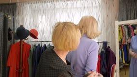 Η ανώτερη γυναίκα προσπαθεί στην αίθουσα εκθέσεως μόδας περιδεραίων απόθεμα βίντεο