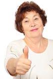 Η ανώτερη γυναίκα στα drees εμφανίζει μεγάλο δάχτυλο Στοκ Φωτογραφία