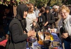 Η ανώτερη γυναίκα στο μαύρο headscarf χύνει το κρασί που γίνεται στη μονή Στοκ εικόνα με δικαίωμα ελεύθερης χρήσης
