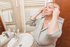 Η ανώτερη γυναίκα σχετικά με το μαλακό δέρμα προσώπου της και τρίβει, κοιτάζοντας στον καθρέφτη στο σπίτι στοκ εικόνα με δικαίωμα ελεύθερης χρήσης