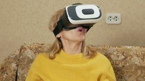 Η ανώτερη γυναίκα φορά τα γυαλιά της εικονικής πραγματικότητας και της προσοχής ενός κινηματογράφου Κοιτάζει γύρω από και θέλει ν φιλμ μικρού μήκους