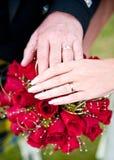 Η ανώτερη εκμετάλλευση ζεύγους παραδίδει έναν γάμο κόκκινο αυξήθηκε ανθοδέσμη Στοκ Φωτογραφία