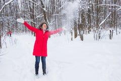 Η ανώτερη ηλικιωμένη γυναίκα ρίχνει το χιόνι στο ξύλο στο κόκκινο παλτό Στοκ Εικόνες