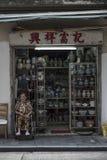 Η ανώτερη κινεζική γυναίκα κάθεται από το κατάστημα οικογενειακής κεραμικής στο Χονγκ Κονγκ στοκ εικόνα