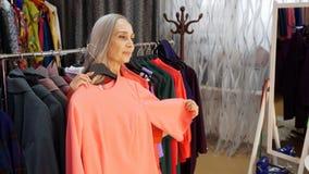 Η ανώτερη κομψή γυναίκα δοκιμάζει το ρόδινο φόρεμα στο κατάστημα ενδυμάτων απόθεμα βίντεο