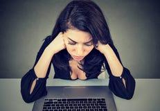 Η απελπισμένη επιχειρηματίας ανησύχησε μετά από τη συνεδρίαση πτώχευσης στο γραφείο στο γραφείο της μπροστά από το lap-top Στοκ Φωτογραφία