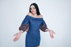 Η απληροφόρητη αμφισβητήσιμη γυναίκα διαδίδει τα χέρια, αυξάνει τα φρύδια με το δισταγμό, που ντύνονται στη μοντέρνη εξάρτηση, αι στοκ φωτογραφίες με δικαίωμα ελεύθερης χρήσης