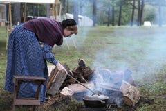 Η αποικιακή γυναίκα τείνει την πυρκαγιά Στοκ Εικόνες