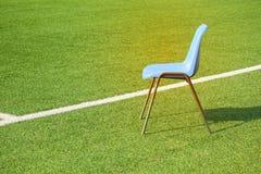 Η απομονωμένη μπλε καρέκλα είναι στην άκρη της άσπρης γραμμής στο αγωνιστικό χώρο ποδοσφαίρου στοκ εικόνες