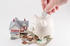 Η αποταμίευση που χτίζει/αγοράζει ένα σπίτι/ένα σπίτι Τράπεζα Piggy με το νόμισμα που είναι Στοκ Φωτογραφία
