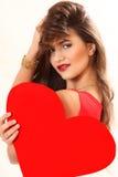 Η αποτελεσματική νέα γυναίκα σε ένα κόκκινο φόρεμα με την κόκκινη καρδιά Valentin στοκ φωτογραφία