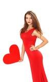 Η αποτελεσματική νέα γυναίκα σε ένα κόκκινο φόρεμα με την κόκκινη καρδιά Valentin Στοκ φωτογραφίες με δικαίωμα ελεύθερης χρήσης