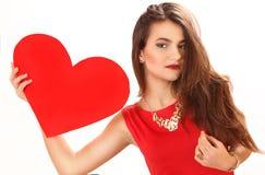 Η αποτελεσματική νέα γυναίκα σε ένα κόκκινο φόρεμα με την κόκκινη καρδιά Valentin Στοκ Φωτογραφίες