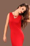 Η αποτελεσματική νέα γυναίκα σε ένα κόκκινο φόρεμα στοκ εικόνα με δικαίωμα ελεύθερης χρήσης