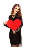 Η αποτελεσματική νέα γυναίκα σε ένα μαύρο φόρεμα με την κόκκινη καρδιά Valent Στοκ εικόνες με δικαίωμα ελεύθερης χρήσης