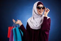 Η αραβική γυναίκα στα γυαλιά ηλίου κρατά ότι το έγγραφο χρωμάτισε τις τσάντες στοκ φωτογραφία