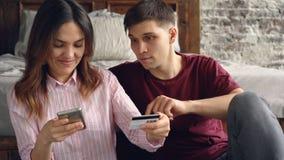 Η αρκετά ασιατική γυναίκα ψωνίζει on-line πληρώνοντας με την τραπεζική κάρτα χρησιμοποιώντας το smartphone αγκαλιάζοντας έπειτα τ απόθεμα βίντεο
