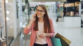 Η αρκετά γυναίκα σπουδαστής μιλά στους φίλους στο κινητό τηλέφωνο και απολαμβάνει τη συνομιλία περπατώντας στη μεταφορά λεωφόρων  απόθεμα βίντεο