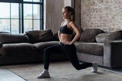 Η αρκετά κατάλληλη γυναίκα που κάνει μετωπικά lunges ή η στάση οκλαδόν ασκεί στο εσωτερικό σε ένα επίπεδο Στοκ εικόνα με δικαίωμα ελεύθερης χρήσης