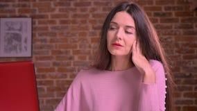 Η αρκετά καυκάσια επιχειρησιακή γυναίκα εργάζεται σκληρά και χασμουρητά καθμένος στο ρόδινο πουλόβερ στον πίνακα απόθεμα βίντεο