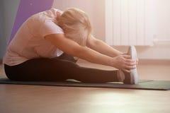 Η αρκετά μέση ηλικίας γυναίκα κάνει το τέντωμα μετά από ένα workout στοκ φωτογραφίες