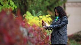 Η αρκετά νέα γυναίκα, γοητεία χαμογελά και παίρνει μια φωτογραφία χρησιμοποιώντας το κινητό τηλέφωνο στο πάρκο φθινοπώρου φιλμ μικρού μήκους