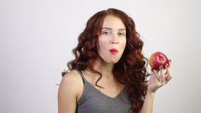 Η αρκετά νέα γυναίκα δαγκώνει το κόκκινο φρέσκο μήλο στο άσπρο στούντιο, βίντεο με τον ήχο φιλμ μικρού μήκους
