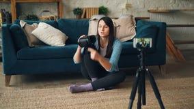 Η αρκετά νέα γυναίκα καταγράφει το βίντεο για τα τεχνητά γυαλιά πραγματικότητας που κρατούν τη συσκευή και που μιλούν την εξέταση φιλμ μικρού μήκους