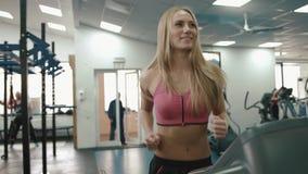 Η αρκετά νέα γυναίκα με τον καλό αριθμό θερμαίνει treadmill στη σύγχρονη γυμναστική Πορτρέτο κινηματογραφήσεων σε πρώτο πλάνο 4K απόθεμα βίντεο