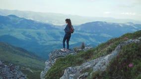 Η αρκετά νέα γυναίκα με το σακίδιο πλάτης, στην αθλητική ένδυση που περιπλανιέται στα βουνά, στέκεται στο επικίνδυνο ύψος και απο απόθεμα βίντεο
