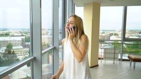Η αρκετά νέα γυναίκα μιλά στο τηλέφωνο και το γυρίζει έπειτα που φαίνεται μακριά έξω μεγάλο παράθυρο απόθεμα βίντεο