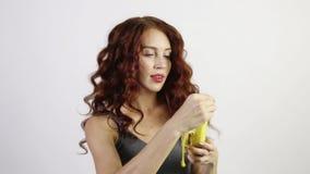 Η αρκετά νέα γυναίκα ξεφλουδίζει και τρώει την μπανάνα στο άσπρο στούντιο, απόθεμα βίντεο