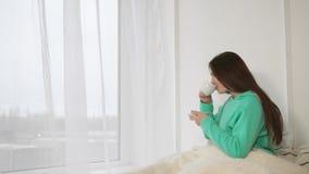 Η αρκετά νέα γυναίκα πίνει τον καφέ στο κρεβάτι της το πρωί απόθεμα βίντεο