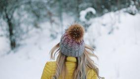 Η αρκετά νέα γυναίκα περπατά γύρω από ένα χειμερινό δάσος και κοιτάζει πέρα από το χαμόγελο ώμων της φιλμ μικρού μήκους