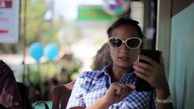 Η αρκετά νέα γυναίκα που χρησιμοποιεί το κινητό τηλέφωνό της κάθεται στον καφέ οδών 1920x1080 απόθεμα βίντεο