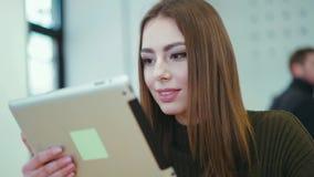 Η αρκετά νέα γυναίκα σε ένα μοντέρνο πουλόβερ κάθεται στο café, πίνει τον καφέ, τα κείμενα τα μηνύματα με την ταμπλέτα της και τ απόθεμα βίντεο