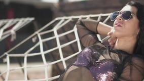 Η αρκετά νέα γυναίκα στο ασημένιο κοστούμι swimmimg κάνει ηλιοθεραπεία την τοποθέτηση στο κρεβάτι σχοινιών Ελεύθερος χρόνος της χ απόθεμα βίντεο
