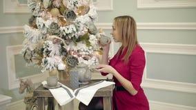 Η αρκετά νέα γυναίκα στο κόκκινο φόρεμα κάθεται στον πίνακα κοντά στο νέο δέντρο έτους και πίνει το τσάι ή τον καφέ φιλμ μικρού μήκους