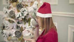Η αρκετά νέα γυναίκα στο κόκκινο φόρεμα κάθεται στον πίνακα κοντά στο νέο δέντρο έτους και πίνει το τσάι ή τον καφέ απόθεμα βίντεο